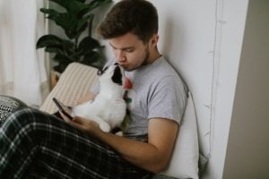 Handsome man sitting with cat and holding phone in hand in stylish modern room