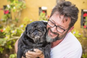 Outdoor nice portrait of adult caucasian man with dog